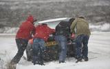 Pushing car stuck in snow