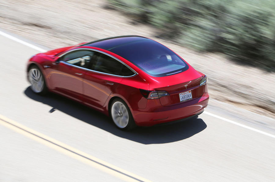 Tesla Model 3 2018 road test review on the road rear left